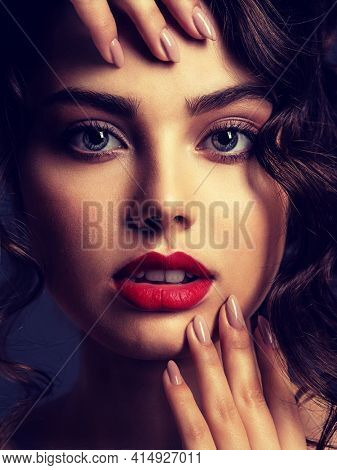 Closeup Face of a beautiful woman with a smoky eye makeup and red lipstick. Sexy brunette girl  with long curly hair. Portrait of an attractive female -  at studio. Fashion model. Beautiful eyes.