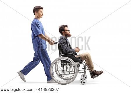 Full length profile shot of a young male nurse pushing a man in a wheelchair isolated on white background
