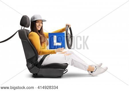 Young female in a the driver seat holding the steering wheel and a learner plate isolated on white background