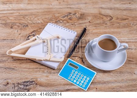 A Small Coffee Cup On A Saucer Stands On A Wooden Table Next To A Notebook And A Pen, Calculator And