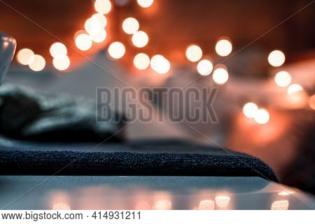 Blanket On A Table With Faded Background Lights And Reflection