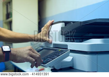 Hand Of Man Is Pressing The Start Button To Using A Photocopier To Copy Document