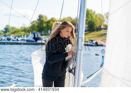 Beautiful Blonde Female Athletes Pull Ropes To Set The Sail On The Mast On The Yacht Before The Trip