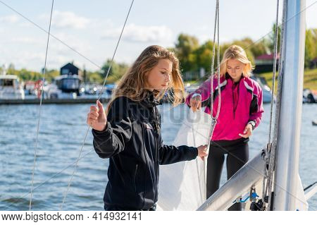 Two Young Blonde Girls On A Sunny Summer Day On A Sailing Boat Are Preparing For A River Trip