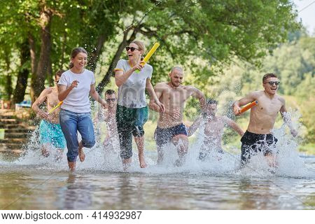 group of happy friends having fun on river