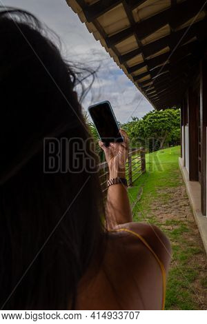 Woman Making Selfie With Cellphone At Her Country House. Cellphone With Black Screen.