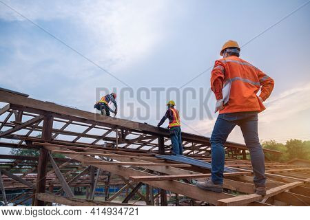 Engineer Technician Watching Team Of Roofer Working On Roof Structure Of Building In Construction Si