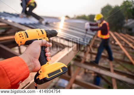 Selective Focus Roofing Tools, Roofer Worker Holding Electric Drill Used On New Roofs With Metal She