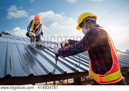 Two Roofer Worker Safety Wear Using Air Or Pneumatic Nail Gun And Installing On New Roof Metal Sheet