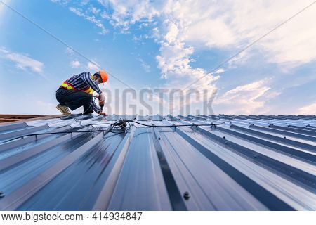 Roof Construction Concept, Roofer Using Air Or Pneumatic Nail Gun And Installing On New Roof Metal S