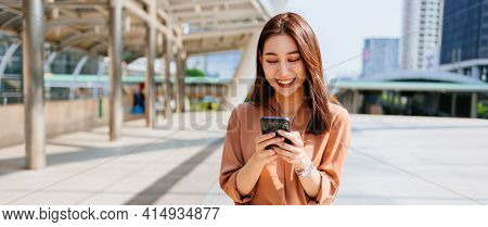Beautiful Young Asian Woman In Formal Clothing Standing Outside Office Building Using Smartphone Whi