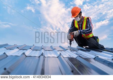 Roofer Working On Roof Structure Of Building In Construction Site, Roofer Using Air Or Pneumatic Nai