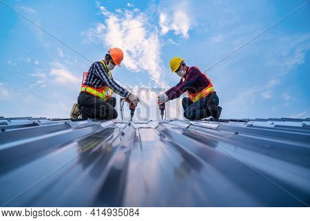 Team Work Construction Worker Safety Wear Using Electric Drill Tools Install On New Roof Metal Sheet