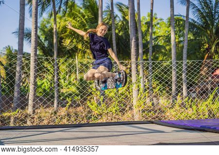 Young Woman On A Soft Board For A Trampoline Jumping On An Outdoor Trampoline, Against The Backdrop
