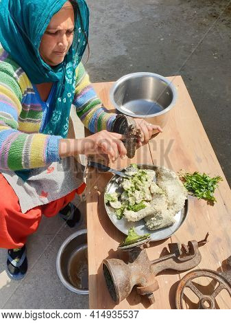 A Indian Woman Taking Out Wet Urad Dal (black Gram) From An Old Hand Grinding Mill Machine At Home,