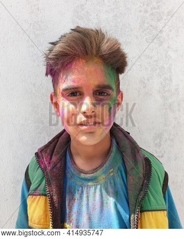 Closeup Shot Of A Indian Kid With Multi Colored Powder On His Face During Holi Festival, Kid Celebra