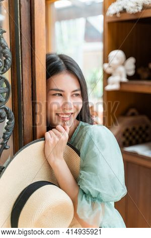 Happy Young Beautiful Woman Leaning At Her Door Frame Of Her House While Holding Her Straw Hat And S
