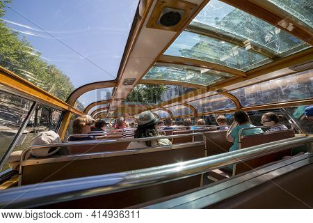 Amsterdam, Netherlands - July 02, 2018: Tourists Inside The Pleasure Boat In Amsterdam