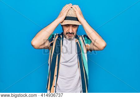 Middle age handsome tourist man on vacation wearing shirt and hat over blue background with hand on head, headache because stress. Suffering migraine.