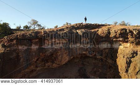 Young Female Traveller Sitting Front To Spectacular Cliff Precipice At Sunrise Falling Over Charles