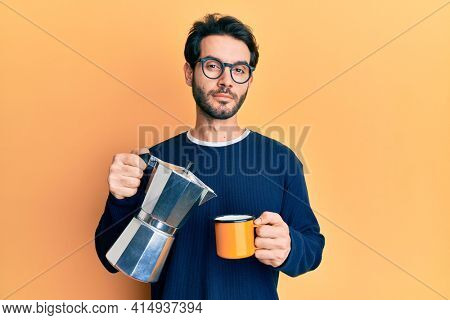 Young hispanic man drinking italian coffee relaxed with serious expression on face. simple and natural looking at the camera.