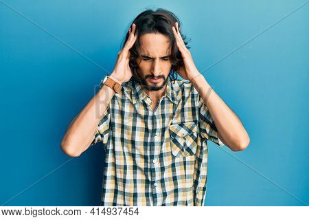 Young hispanic man wearing casual clothes with hand on head for pain in head because stress. suffering migraine.