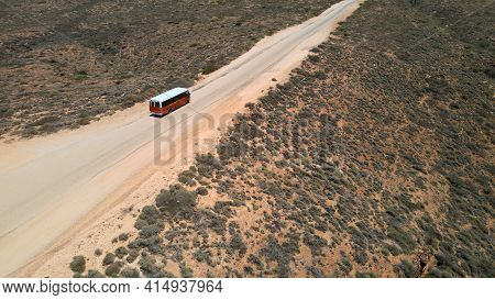 Aerial Shot Of 4x4 Safari Vehicle Driving On Hilly Desert During Sunlight. Exmouth, Western Australi