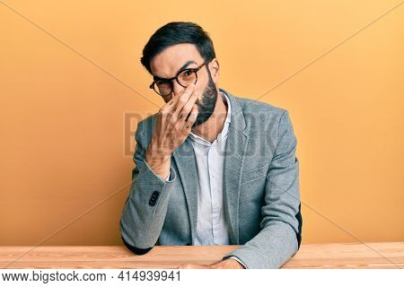 Young hispanic man working at the office smelling something stinky and disgusting, intolerable smell, holding breath with fingers on nose. bad smell