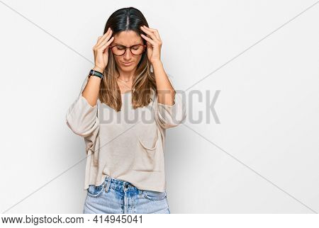 Young woman wearing casual clothes and glasses with hand on head for pain in head because stress. suffering migraine.