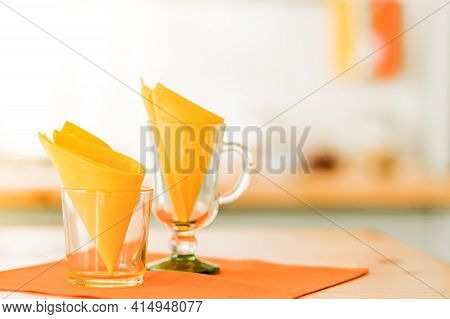 Glass Cups Decorated With Yellow Napkins Stand On The Table On Orange Napkins. Sunlight In The Room