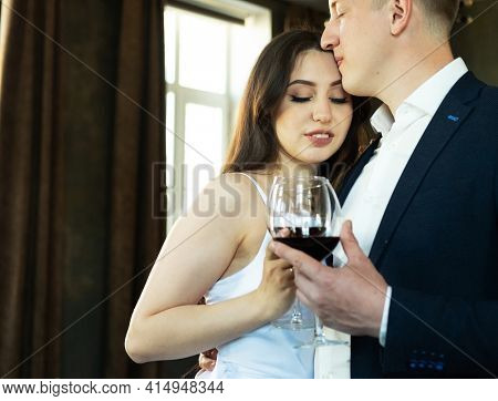 Family and young people concept: Young newlywed couple drinking wine and smiling at their happiness, romance and tenderness