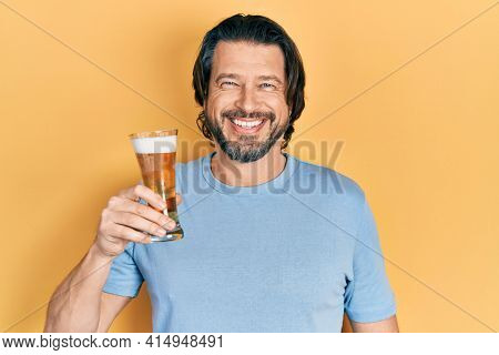 Middle age caucasian man drinking a pint of beer looking positive and happy standing and smiling with a confident smile showing teeth