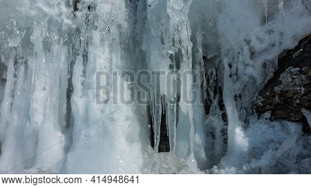 Spring Melting Snow. Close-up. Full Screen. Icicles Of Bizarre Shape Shine Under The Rays Of The Sun