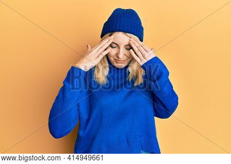 Young caucasian woman wearing wool winter sweater and cap with hand on head, headache because stress. suffering migraine.