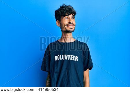 Young hispanic man wearing volunteer t shirt smiling looking to the side and staring away thinking.