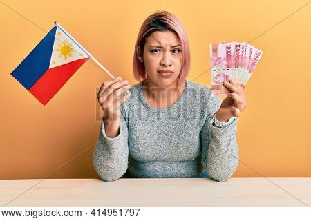 Hispanic woman with pink hair holding philippine flag and philippines pesos banknotes skeptic and nervous, frowning upset because of problem. negative person.