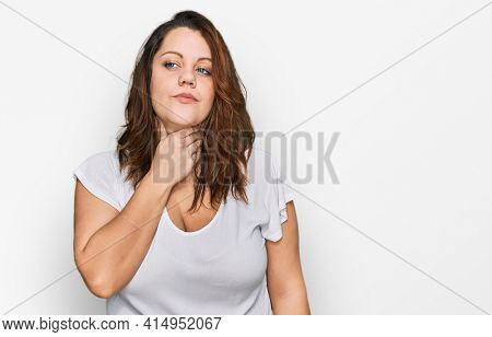 Young plus size woman wearing casual white t shirt touching painful neck, sore throat for flu, clod and infection