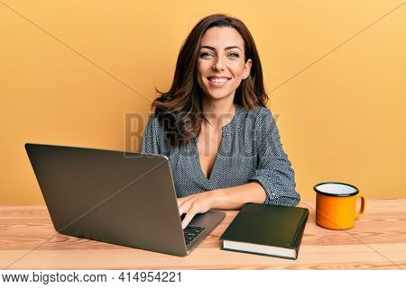 Young brunette woman working using computer laptop looking positive and happy standing and smiling with a confident smile showing teeth
