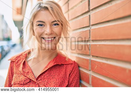 Young blonde woman smiling happy leaning on the wall at the city.