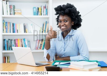 Happy African American Student Or Business Trainee Working At Computer At Desk At Office