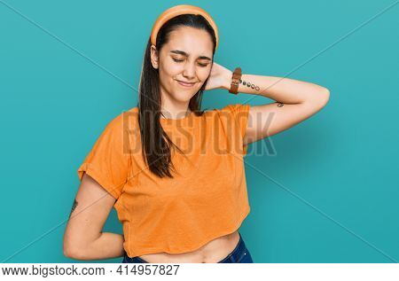 Young hispanic woman wearing casual clothes suffering of neck ache injury, touching neck with hand, muscular pain