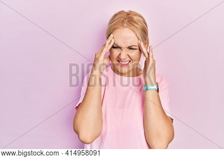 Young blonde woman wearing casual pink t shirt with hand on head, headache because stress. suffering migraine.