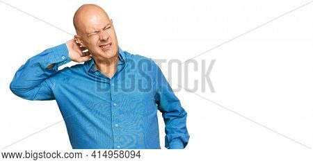 Middle age bald man wearing casual clothes suffering of neck ache injury, touching neck with hand, muscular pain
