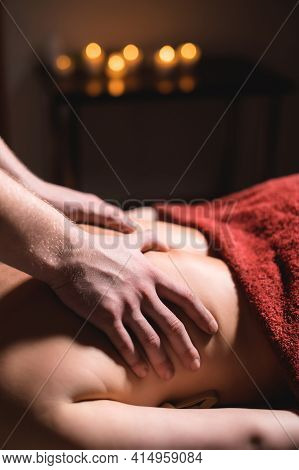 Massage Of A Female Back In A Dark Room Of A Spa Salon. Male Masseur Doing Massage Of The Back Of Th