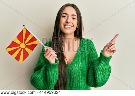 Young hispanic girl holding macedonian flag smiling happy pointing with hand and finger to the side
