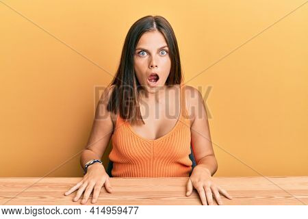 Young caucasian woman wearing casual clothes sitting on the table afraid and shocked with surprise and amazed expression, fear and excited face.