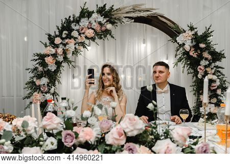 Wedding Couple Doing Silfi At The Wedding Table. Happy Lovers Are Photographed On The Phone During A