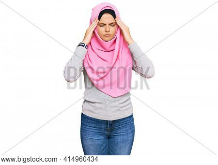 Young caucasian woman wearing traditional islamic hijab scarf suffering from headache desperate and stressed because pain and migraine. hands on head.