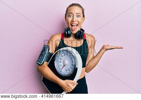 Beautiful young blonde sporty woman holding weight machine to balance weight loss celebrating crazy and amazed for success with open eyes screaming excited.