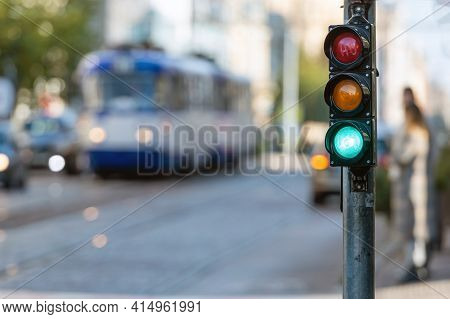 Blurred View Of City Traffic With Traffic Lights, In The Foreground A Traffic Light With A Green Lig